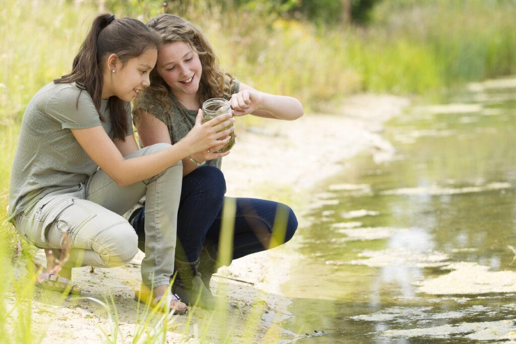 Kinder mit Becherlupe am Gewässer